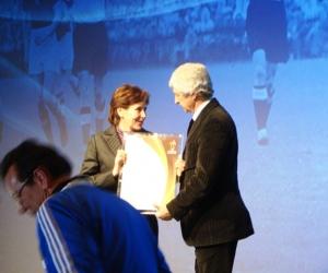 Bajakiné Kovács Margit átveszi a Europe Best Grassroots project díjat Gianni Rivera kíváló volt labdarúgótól.